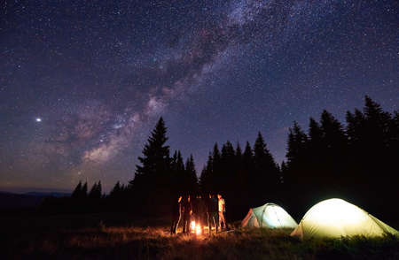 Group of five tourists are standing around burning campfire near two tents against backdrop pine forest under starry sky. Dark night sky is strewn with bright stars and Milky Way is visible on it.