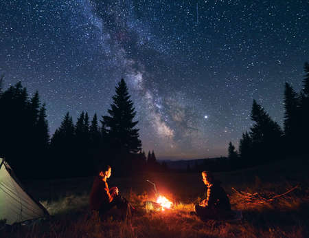 Man and woman communicate by fire against starry sky with bright Milky way. Night camping. Silhouettes of big fir trees against backdrop of mountain valley under an incredible sky
