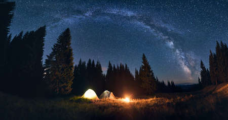 Panoramic view of night camping in valley with large pine trees. Burning campfire and illuminated tourist tents under bright starry sky on which the Milky Way is clearly visible. Mighty landscape