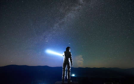 Cosmonaut wearing white space suit and helmet directs a blue ray of light into starry sky above horizon in the night, standing with his back to the camera in the mountains, space travel concept