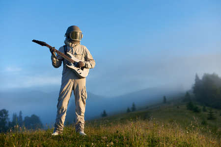 Astronaut wearing white space suit and helmet playing white guitar, standing on sunny green mountain glade in morning. Foggy hills, blue sky on background. Concept of astronautics, music and nature.