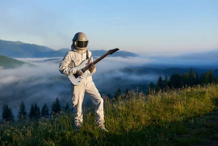 Cosmonaut wearing white space suit and helmet playing white guitar, standing on sunny green mountain glade in summer, morning fog rising up from the valley behind him. Concept of astronautics, music Stok Fotoğraf