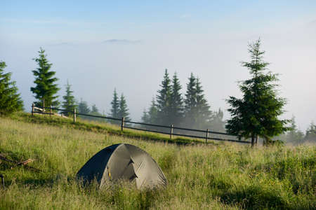Beautiful view of tourist tent laid out on a green hill in the summer mountains in sunny morning. Scenic landscape of hiker campsite in valley with green grass. . Concept of travel, hiking and camping