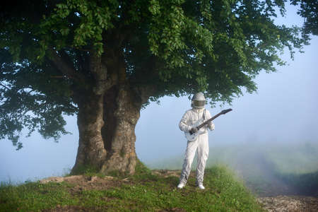 Space traveler playing on guitar near large tree. Astronaut guitarist wearing white space suit and helmet while standing in misty valley with big tree. Concept of music, astronautics and nature. Stok Fotoğraf