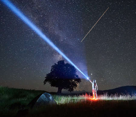 Illuminated spaceman in space suit and helmet directs a ray of light into the night sky full of stars with help of lantern near tourist camping. Tourist tent, big tree, shooting star