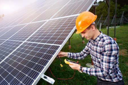 Man in a helmet uses a sensor to check the solar station. Power station. Home construction. Technology concept. Stok Fotoğraf