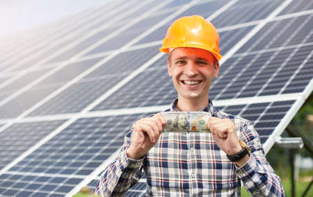 Satisfied worker with hundred dollar bill in hand against the solar station. Business and generation concept. Green ecological power energy generation.