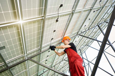 Solar power station with large volumes. The young man inside her is setting up a system. A guy in an orange uniform and a helmet on his head. Solar station development concept. Stok Fotoğraf