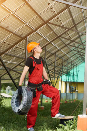 Male technician looking up at the solar panels with a coil of wires in his hands on a plot near the house. Worker in orange uniform, black t-shirt and gloves. The concept of modern construction