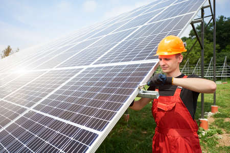 Male technician checks the maintenance of the solar panels. Orange safety cap on his head. Concept: renewable energy, technology, electricity, service, green power.
