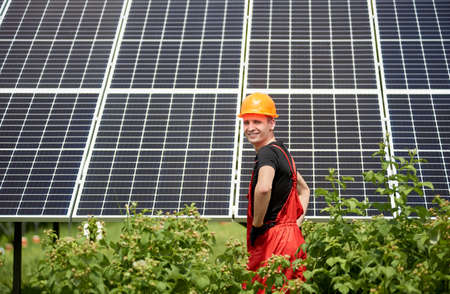 Engineer standing in yellow construction helmet front solar photovoltaic power station at sunny day with greenery. Technician worker installing solar panels. Alternative energy ecological concept.