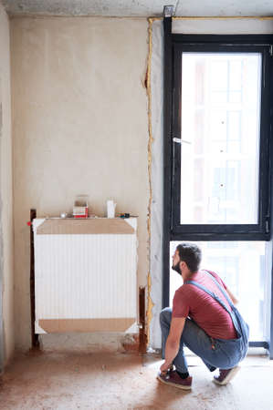 Plumber installing water radiator in new empty room next to window. Fitting lower valve. Male worker during installation process. Construction, maintenance, home refurbishment concept