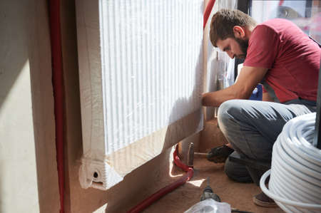 Young plumber connecting water radiator to heating system in new unfinished apartment. Crouching man working with hammer. Copy space. Concept of home renovation and heating system installation. Stok Fotoğraf