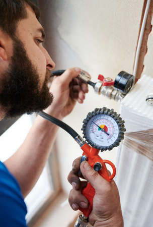 Close up of bearded man filling pipes with pressurized air to inspect for leaks in new installation. Worker using manometer, checking gas tightness of heating system. Concept of gas tightness testing. Stok Fotoğraf