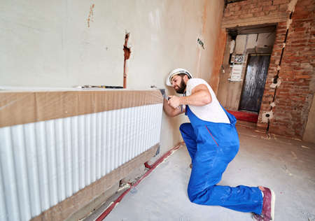Plumber, wearing blue overalls, white helmet, installing water radiator, working with wrench. Maintenance repair works renovation in the flat. Wide angle. Construction and home renovation concept. Stok Fotoğraf