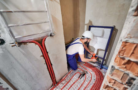 Wide angle photography of young plumber working in unfinished apartment, installing flush tank. Man wearing blue uniform and white helmet. Red pipes on the floor, new hanging radiator on the wall Imagens