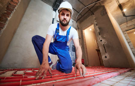 Wide and low angle view portrait of young plumber wearing blue overalls and white helmet, tying up red tubes on the floor heating system in new unfinished apartment. Concept of home renovation.