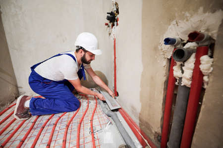 Wide angle view on young worker standing on his knees in blue overalls and helmet installing underfloor heating system and plumbing system. Concept of home renovation and plumbing works. Stok Fotoğraf