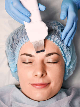 Close up of beautician hands in sterile gloves using ultrasonic scrubber while cleaning female client face. Woman having deep cleaning skincare procedure in beauty salon. Concept of skincare treatment