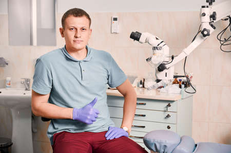 Front view of young man dentist in sterile gloves looking at camera and showing approval gesture. Male stomatologist in blue shirt sitting near dental diagnostic microscope. Concept of dentistry. Stok Fotoğraf