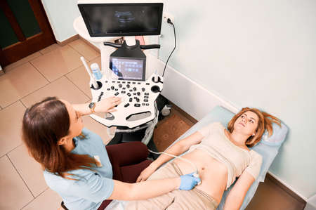 Top view of female patient lying on daybed while having ultrasonography procedure in clinic. Woman sonographer doing abdominal ultrasound scanning for patient. Concept of healthcare and sonography. Stok Fotoğraf