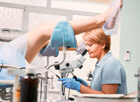 Side view of gynecologist in sterile gloves examining woman with colposcope in gynecological cabinet. Female doctor doing colposcopy examination. Concept of gynecology, medicine and female health.