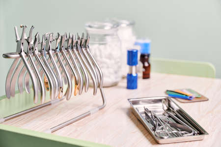 Set of various stainless steel instruments for braces and dental treatment. Silver removing pliers, cutters, removers, forceps, other orthodontic tools on desk in dental clinic. Concept of dentistry.
