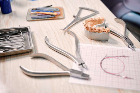 Desk with orthodontic tools, ligature ties, dental teeth model and wire braces drawing. Ligature wire cutters, pliers, multicolored teeth correctors and lower jaw model on table in dental office. Stok Fotoğraf