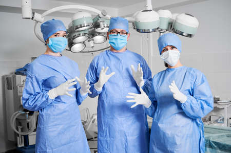 Front view of three doctors in operating room, surgeons ready for plastic surgery in clinic, wearing sterile gloves, blue surgical uniform, protective face mask. Concept of medicine healthcare workers