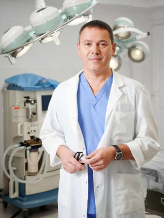 Portrait of man surgeon looking at camera, standing in operating room in hospital. Handsome male doctor wearing white lab coat. Concept of medicine, medical workers and plastic surgery. Stok Fotoğraf