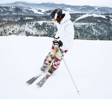 Image of skier in ski equipment, captured in motion doing trick in snowy mountains in full length. Beautiful landscape. Winter sports concept