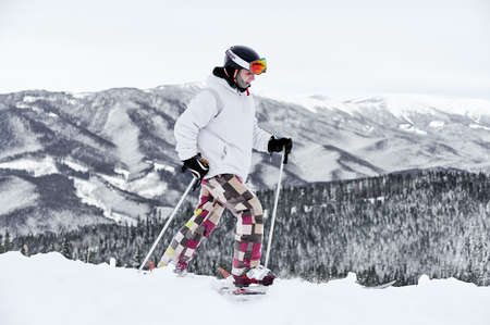 Horizontal snapshot of young skier in colorful costume walking along snowy hill against amazing mountains, ski tour. Side view, copy space, full length
