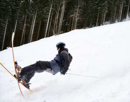 Side view snapshot of skier sliding down the piste along spruce forest. Moment of fall down on snow. Concept of extreme kinds of sport . Season entertainment