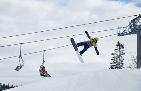 Snowboarder doing tricks in the mountains during winter season, flying up high with snowboard against chairlift and sky. Concept of extreme kinds of sport. Low angle view