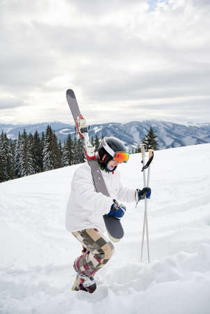 Full length of alpine skier in white winter jacket holding skis and ski poles. Young man in helmet and ski goggles climbing snow-covered hill in winter mountains. Concept of winter sport activities.