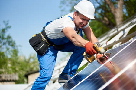 Technician connecting solar photo voltaic panel to metal platform using screwdriver on bright blue sky background. Stand-alone solar panel system installation concept. Stok Fotoğraf