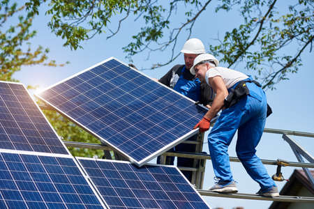 Two young technicians mounting heavy solar photo voltaic panel on tall steel platform on green tree background. Exterior solar panel voltaic system installation, dangerous job concept.