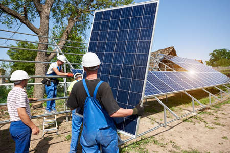 Team of four technicians working on exterior voltaic solar panel system installation in rural countryside on bright sunny summer day. Renewable ecological cheap green energy production concept.