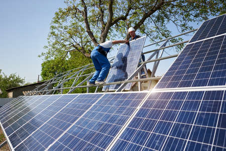 Two workers on tall steel platform mounting heavy solar photo voltaic panel on green tree and blue sky background. Exterior solar panel system installation, efficiency and professionalism concept.