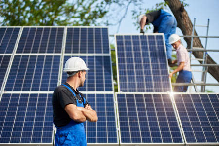 Profile of young engineer technician standing in front of unfinished high exterior solar panel. Photo voltaic system blue shiny surface watching team of workers on high steel platform.