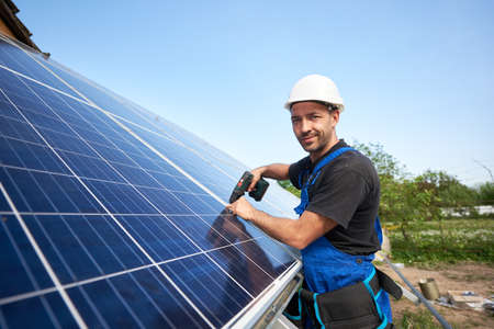 Smiling technician mounting solar panel to metal platform using electrical screwdriver on blue sky copy space background. Stand-alone solar system installation, efficiency concept.