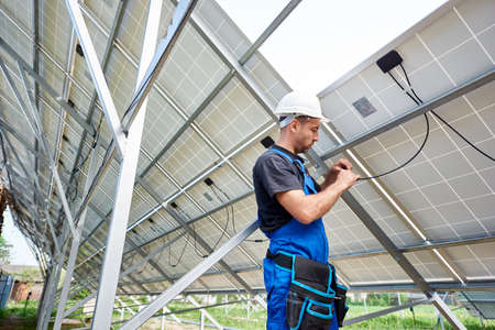 Young engineer technician making electrical wiring standing inside high exterior solar panel photo voltaic system on bright sunny summer day. Eco friendly cheap electricity generation concept. Stok Fotoğraf