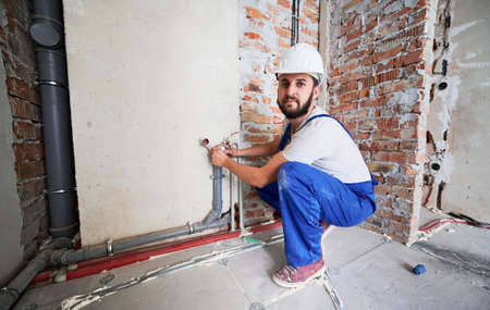 Bearded young man in work overalls installing heating pipes in apartment, looking to the camera. Male worker in safety helmet doing maintenance jobs for water and heating systems. Concept of plumbing.