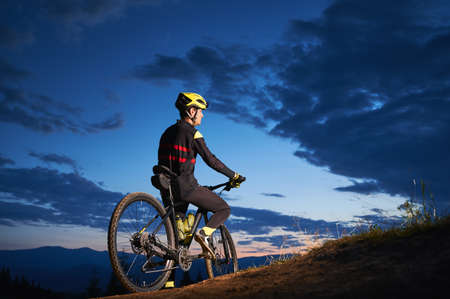 Back view of young man in cycling suit sitting on bicycle under blue night sky with clouds. Male bicyclist in safety helmet riding bicycle on the road in the evening. Concept of active leisure. Stok Fotoğraf