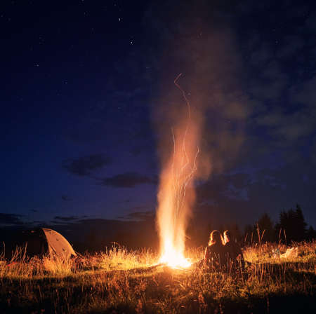 Beautiful view of night starry sky over grassy hill with camp tent, campfire and hikers. Young man and woman tourists having a rest near bonfire. Concept of hiking, night camping and relationship.