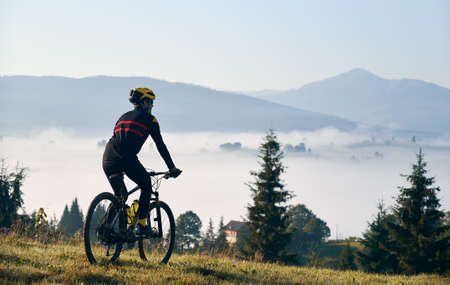 Silhouette of man cyclist in cycling suit riding bike on grassy hill. Male bicyclist enjoying the view of majestic mountains during bicycle ride. Concept of sport, bicycling and nature. Stok Fotoğraf