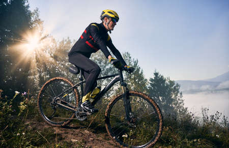 Young sportsman riding his bicycle in the mountains in early foggy morning going downhill. Sun is shining through tree crown, peaks in clouds on background. Concept of active lifestyle Stok Fotoğraf