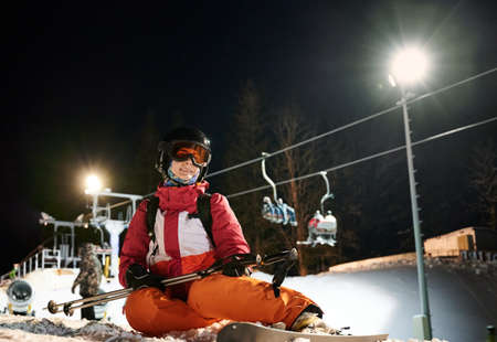 Female skier wearing vivid suit, sitting on snow-covered ski slope, happy and satisfied after freeride. Night ride at ski resort. Concept of night skiing, winter sport activities.