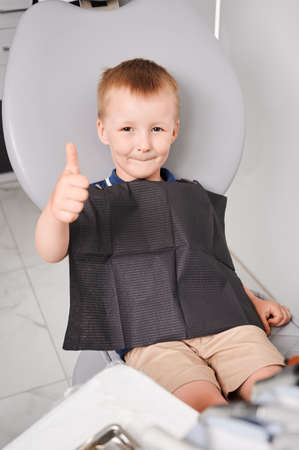 Overhead view on a little patient sitting in dentists chair. Smiling boy, wearing black bib and showing thumb up at dentist office. Vertical snapshot. Healthcare concept Imagens