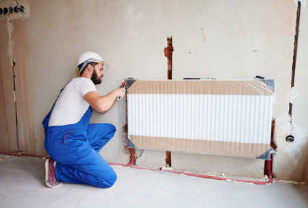 Young plumber, wearing blue overalls, white helmet, installing water radiator in unfinished apartment. Maintenance repair works renovation in the flat. Heating installation. Horizontal snapshot